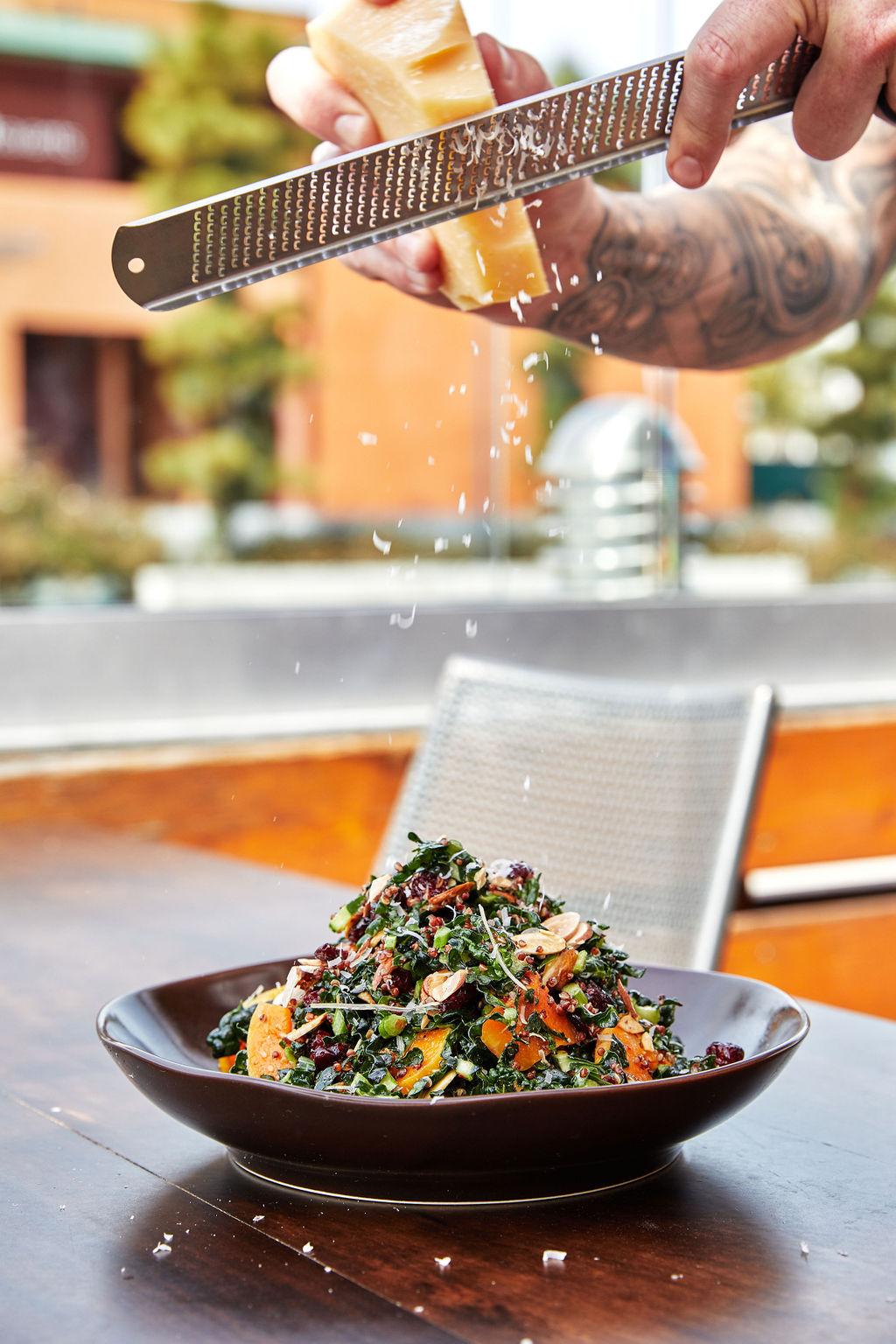 Server grating fresh Parmesan on our Kale Quinoa salad
