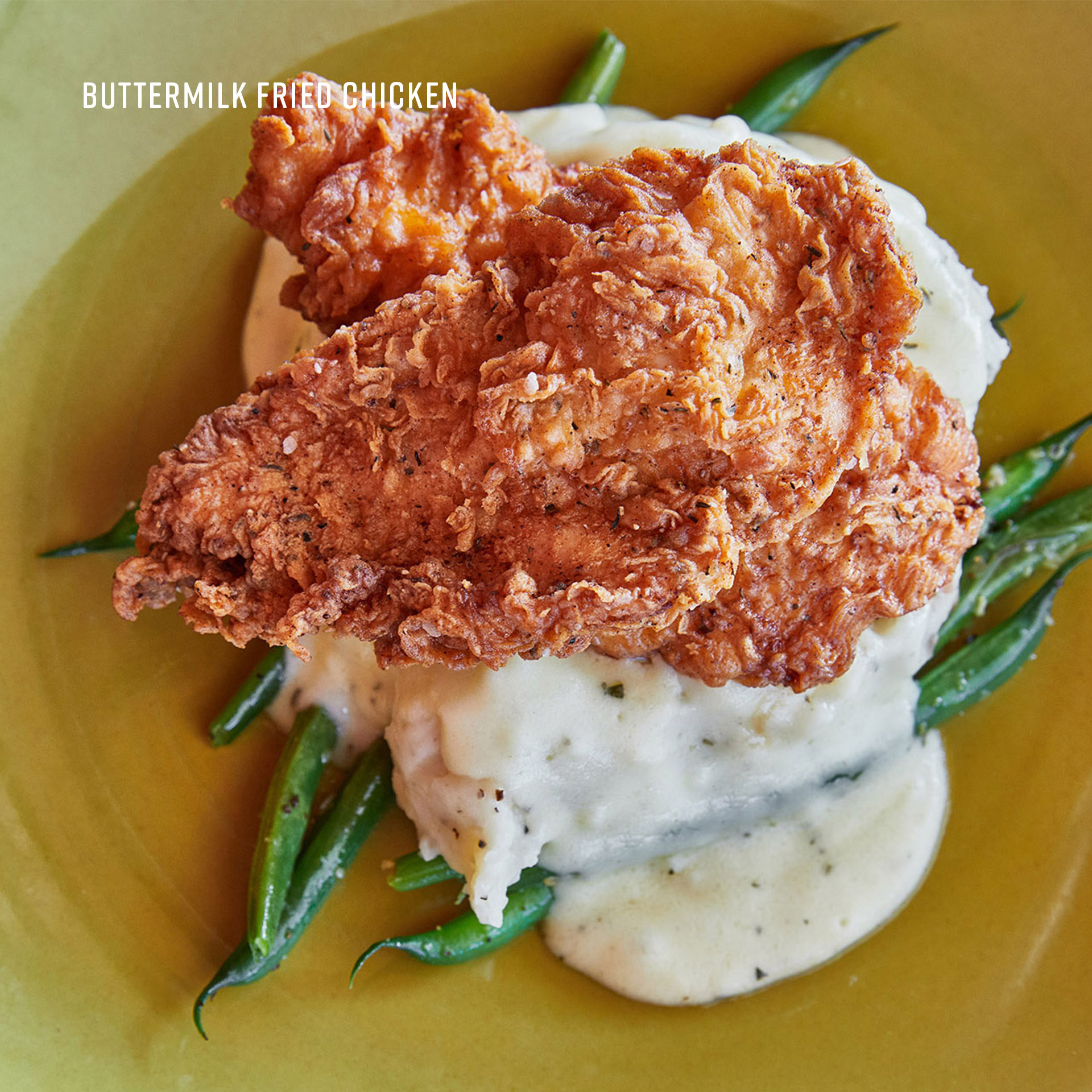 Our beautifully plated Buttermilk Fried Chicken on top of fresh sides